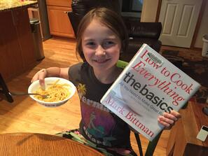 Little girl reading a cookbook and eating a bowl of pasta
