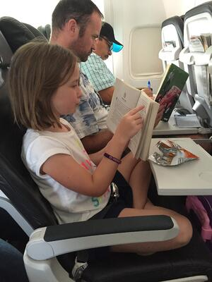 Father and daughter reading books together on the plane